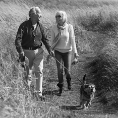 Senior couple walking with dog in the countryside