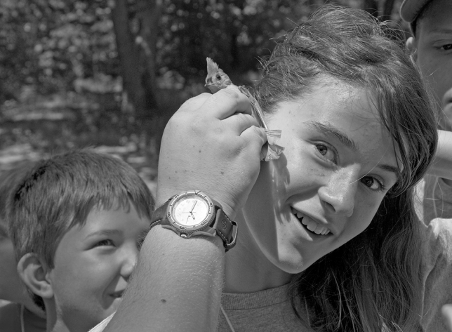 Girl listens to the heartbeat of bird with a naturalist/educator